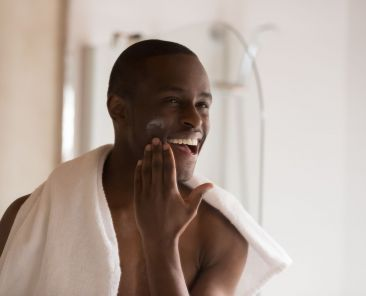 Happy smiling african ethnicity man looking in mirror at bathroom after showering, applying moisturizing after shaving balm on cheek, soothing and soften sensitive skin. Morning hygiene routine.